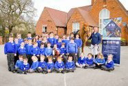 Huxley Primary School Children with top show jumper Anthony Condon in the playground