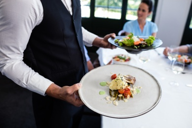 Portrait of waiter standing with meal next to customers